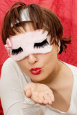 Young attractive woman in sleep mask sending kiss — Stock Photo