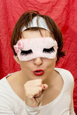 Young woman in sleeping mask imitates singing into a microphone — Stock Photo