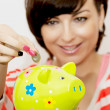 Young woman gives a euro coin into decorative ceramic piggy bank — Stock Photo #43228695
