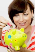 Young woman gives a euro coin into decorative ceramic piggy bank — Stock Photo