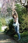 Young joyful woman posing under flowering tree — Stock Photo
