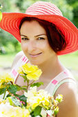 Beautiful woman in a red hat posing in the garden — Stok fotoğraf