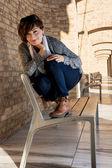 Beautiful young woman posing on a bench — Foto Stock