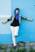 Beautiful positive woman posing in front of a blue wall — Stock Photo