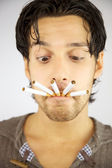 Handsome man with many cigarettes in his mouth ready to smoke addicted — Stock Photo