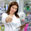 Good looking pharmacist thumb up with tablet in pharmacy — Stock Photo #13733901