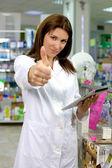 Lindo moreno farmacêutico no polegar farmácia feliz trabalhando com tabela — Fotografia Stock