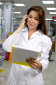 Beautiful pharmacist working in pharmacy with telephone — Stock Photo