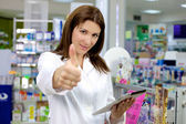 Good looking pharmacist thumb up with tablet in pharmacy — Stock Photo