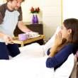 Woman receiving breakfast in bed from husband — Stock Photo