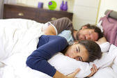 Young woman crying in bed desperate about man sleeping — Stock Photo