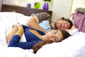 Sad woman in bed with sleeping husband — Stock Photo