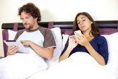 Paar werken in bed met tablet pc- en telefoon — Stockfoto