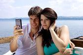 Bella uomo e donna prendendo foto di fronte al lago — Foto Stock