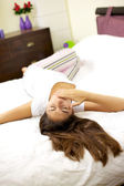 Woman in bed laying tired yawning — Stock Photo
