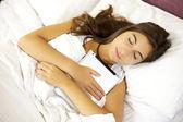 Mladá žena spící vytěžený tabletu v posteli — Stock fotografie