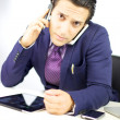 Stock Photo: Young businessman talking with two cell phones