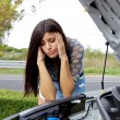 Desperate woman looking at broken engine of her car — Stock Photo #15734429