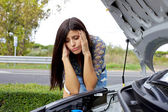 Desperate woman looking at broken engine of her car — Stock Photo