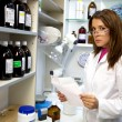 Woman pharmacist working in laboratory reading prescription — Stock Photo