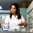 Beautiful female pharmacist searching for medicine — Stock Photo