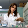 Pharmacist in pharmacy looking medicine and prescription — Stock Photo
