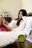 Serious woman in bed reading tablet — Stock Photo