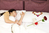 Woman sleeping with San Valentine gifts — Stock Photo