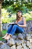 Felice collegio studente lettura libro in un parco — Foto Stock