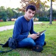 Smiling good looking man with tablet in park — Stok fotoğraf