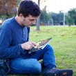 Stock Photo: Man working with tablet in park