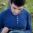 Handsome man working with tablet in park in autumn — Stock Photo