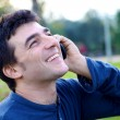 Happy man in park making phone call — Stock Photo