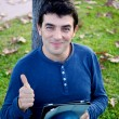 Man thumb up in park with tablet — Stock Photo