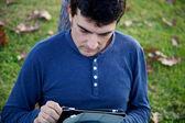 Knappe man aan het werk met tablet in park in het najaar van — Stockfoto