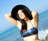 Happy model with hat in the water tanning with bikini — Stock Photo