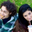 Happy couple eating fast food hamburger and soda in park — Stock Photo