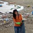 mujer triste con bolsa de basura en la playa sucia — Foto de Stock   #25870863