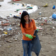 Young activist cleaning dirty beach in nature disaster — Stock Photo #25871153
