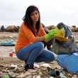 Young woman trying to clean dirty beach ecological disaster — Stockfoto