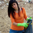 Young woman with bag full of dirt on destroyed dirty beach — Stock Photo #25871561
