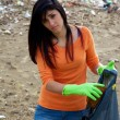 Young woman with bag full of dirt on destroyed dirty beach — Stock Photo