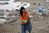 Young activist cleaning dirty beach in nature disaster — Stock Photo