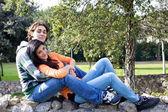 Pareja joven en el parque abrazando y sonriendo — Foto de Stock