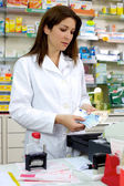 Beautiful brunette pharmacist counting money — Stok fotoğraf