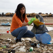 Young social worker cleaning dirty beach — Stock Photo