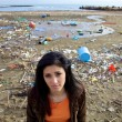 Stock Photo: Sad woman in front of dump and dirty beach
