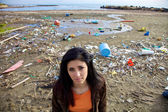 Sad woman in front of dump and dirty beach — Stock Photo