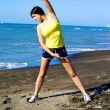 Woman stretching on the beach after running — Stock fotografie