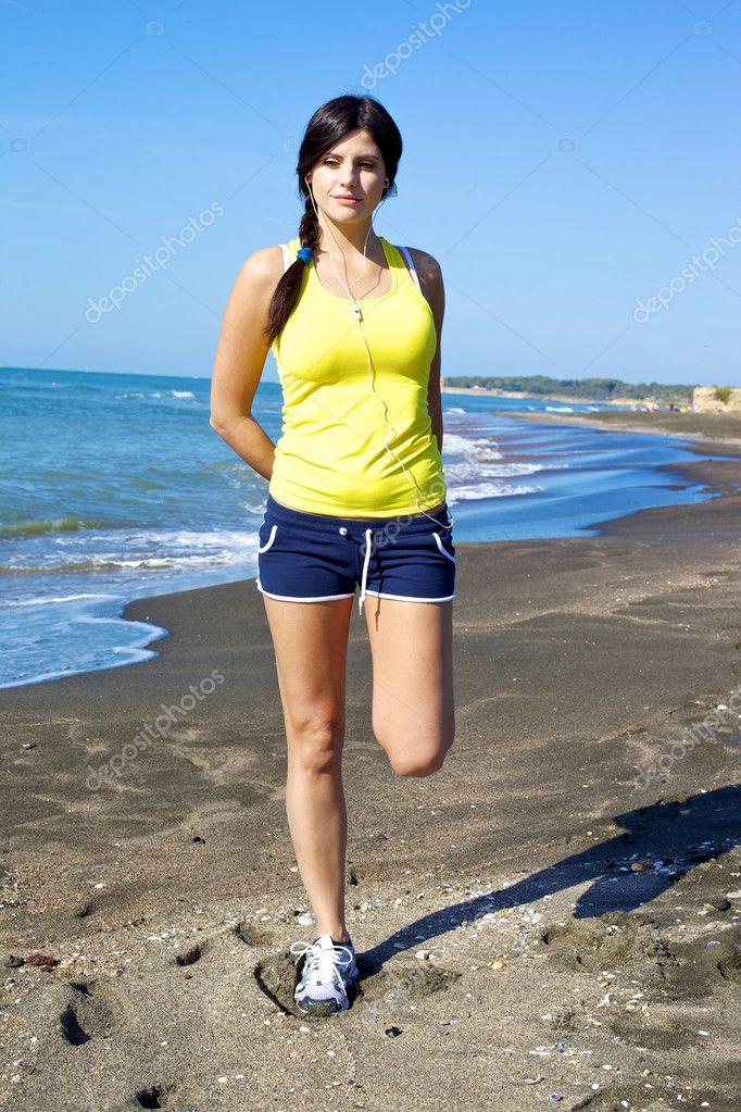 femme tenant la jambe tirement des muscles sur la plage apr s footing photographie. Black Bedroom Furniture Sets. Home Design Ideas